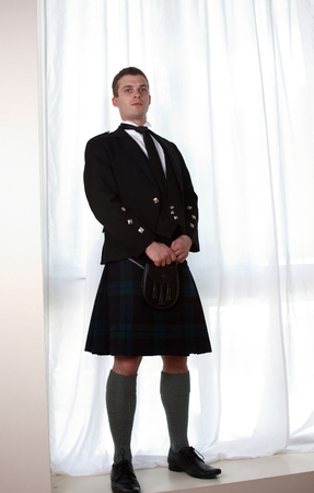 A scottish man standing alone in traditional dress