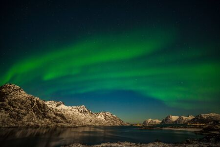 amazing aurora borealis, northern lights, northern lights, over fjord mountains in the North of Europe , Lofoten islands, Norway, long shutter speed.