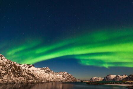 northern lights, Aurora borealis over fjord mountains with many stars on the sky in Lofoten islands, Norway, long shutter speed.