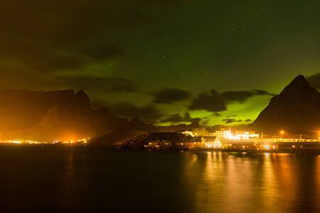 northern lights, Polar lights with many clouds and stars on the sky over village and mountains in the North of Europe , Lofoten islands, Norway, long shutter speed. Stockfoto