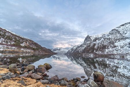 dramatic sunset with cloudy sky under blue hour over fjord on Lofoten islands, Norway. long exposure