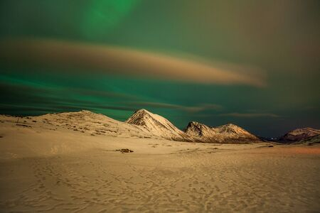 northern lights, Polar lights with many clouds and stars on the sky over mountains in the North of Europe , Tromso, Norway, long shutter speed.