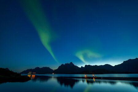 schöne Aurora Borealis. Grüne Nordlichter. Sternenhimmel mit Polarlichtern. Winterlandschaft mit Aurora, Meer mit Himmelsreflexion und schneebedeckten Bergen. lange Verschlusszeit Standard-Bild