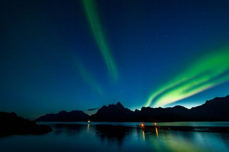 polar lights aurora borealis, northern lights with many stars in the sky over mountains in the North of Europe , Lofoten islands, Norway, long shutter speed. Stock fotó