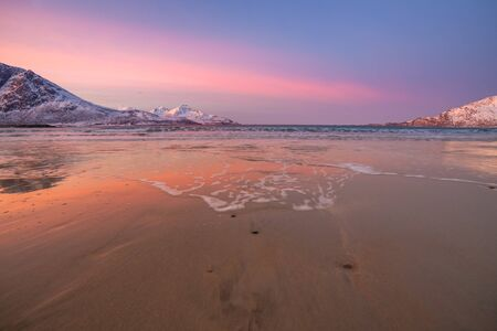 sunrise with amazing magenta color over sand beach and fjord. Tromso, Norway. Winter. Polar night. long shutter speed