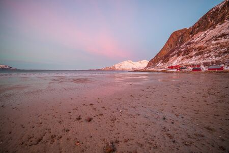 sunrise with amazing magenta color over sand beach and fjord. Tromso, Norway. Winter. Polar night. long shutter speed Stockfoto