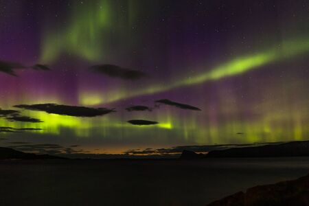 northern lights, Polar lights with many clouds and stars on the sky over fjord mountains in the North of Europe , Lofoten islands, Norway, long shutter speed.