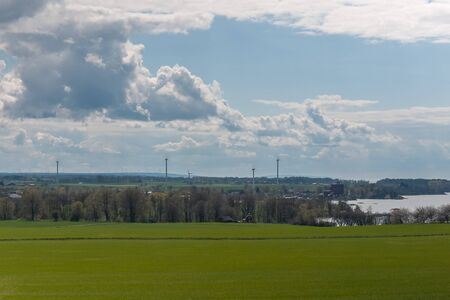 Stormy sky over a green sown field. Beautiful spring landscape with wind power on the background. Central Sweden.