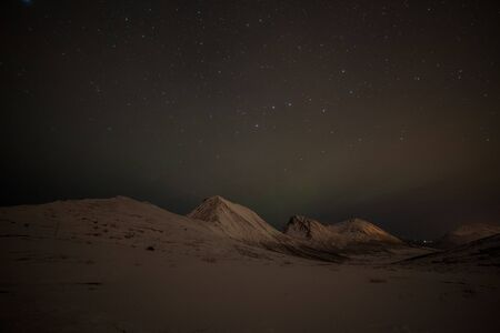 night with many clouds and stars on the sky over mountains in the North of Europe , Tromso, Norway, long shutter speed. Stockfoto