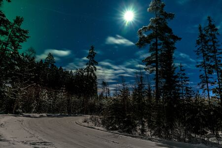 The moon shines on a road running along a winter forest. in the sky clouds and the remnants of the northern lights