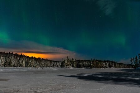 Aurora borealis, northern lights, Polar lights with many clouds and stars on the sky by moonlight over a frozen lake and snowy forest in Sweden. long shutter speed. Stockfoto