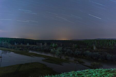 Star traces are reflected in the river during a flood. Spring, Russia. long shutter speed. selective focus Stockfoto