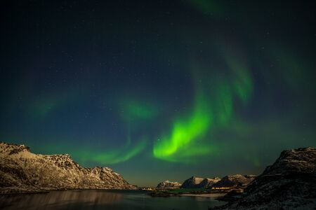 Dramatic northern lights, Aurora borealis over fjord mountains with many stars on the sky in Lofoten islands, Norway, long shutter speed. 免版税图像
