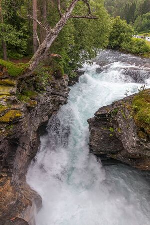 Nature of Norway. Mountain river with clear water. Rocky slope with a picturesque waterfall. Hiking in Norway. Scandinavian nature. Mountain river with a pedestrian bridge. The severe nature of Norway Stock Photo