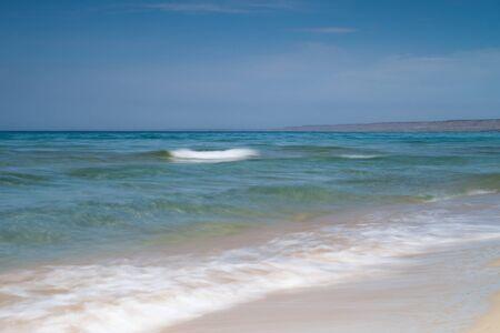 View of blue sea waves at sandy beach. Horizon line. Caspian Sea, sandstone coast. kazakhstan, ustyurt, Selective focus, long shutter speed