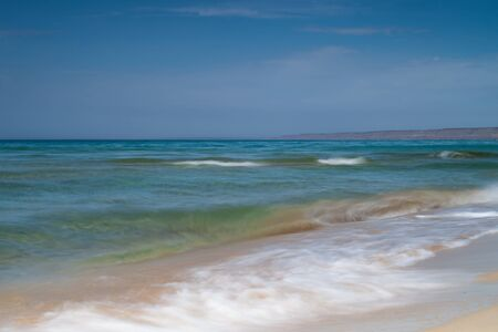 View of blue sea waves at sandy beach. Horizon line. Caspian Sea, sandstone coast. kazakhstan, ustyurt, Selective focus, long shutter speed