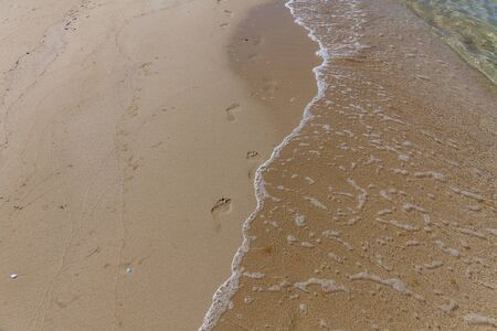 human footprints in the sand on the ocean. Sand texture. Sandy beach for background. Top view