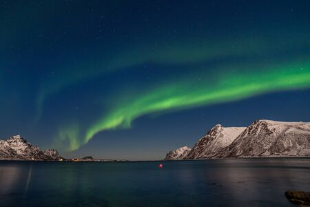 amazing northern lights, Aurora borealis over fjord mountains with many stars on the sky in Lofoten islands, Norway, long shutter speed.