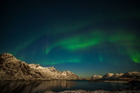 Aurora borealis, Polar lights, Northern lights over fjord mountains with many stars on the sky in the North of Europe , Lofoten islands, Norway, long exposure.