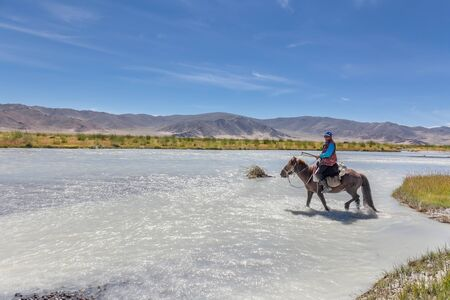 Altai, Mongolia - June 14, 2017: Mongolian nomad crosses a white mountain river on a horse