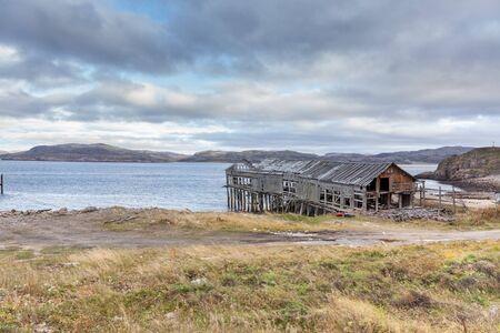 Russia, Arctic, Kola Peninsula, Barents Sea, Teriberka: Run down wooden house building at low tide near fishing harbor of Lodeiny, the newer part of old Russian settlement small fishing village.