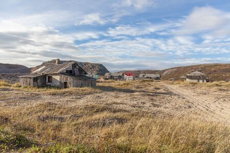 Russia, Arctic, Kola Peninsula, Barents Sea, Teriberka: Run down abandoned wooden house in the city center of the old Russian settlement small fishing village with green grass and grey cloudy sky.