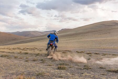 motorbike in the steppes of Mongolia riding. having fun driving the empty road on a motorcycle tour journey.