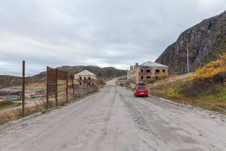 Teriberka, RUSSIA, September 27, 2016: car parked on the road near an abandoned house