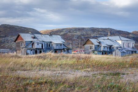 Russia, Arctic, Kola Peninsula, Barents Sea, Teriberka: Run down abandoned wooden house in the city center of the old Russian settlement small fishing village with green grass and grey cloudy sky. Stock Photo
