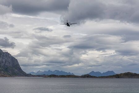 Aircraft in the cloudy sky of the Norwegian fjords, Lofoten