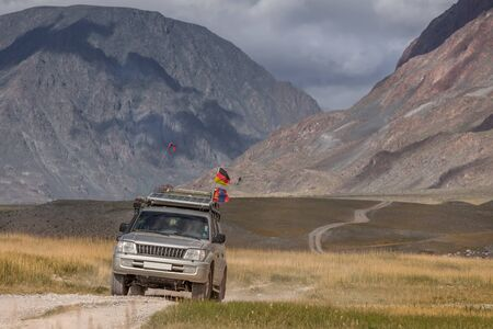 Car with German and Mongolian flags on winding road in the Altai Mountains of Mongolia