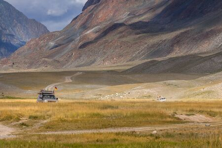 Altai, Mongolia - June 14, 2017: Cars with German and Mongolian flags on winding road in the Altai Mountains of Mongolia