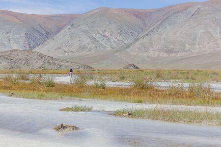 A motorcyclist is crossing white, mountain river on a motorcycle. Mountain Altai, Mongolia Фото со стока
