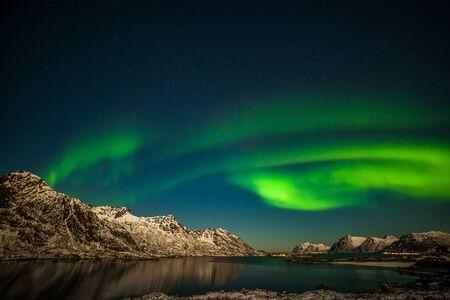 Polarlichter, Aurora borealis über Fjord, Berge mit vielen Sternen am Himmel auf den Lofoten, Norwegen, lange Verschlusszeit.