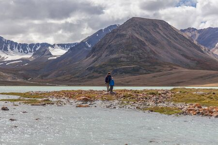 Father and son are walking along the grass near the mountain lake of the Mongolian Altai.