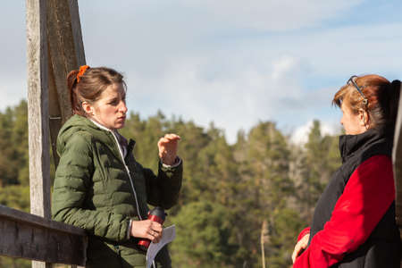 Two women are talking to each other while on a wooden bridge Stockfoto