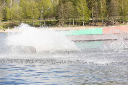 Wakeboarder on wakeboard landed in water surrounded by spray. Wakeboarding is an extreme sport. Stockfoto