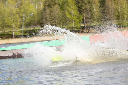 Teen Wakeboarder on wakeboard landed in water surrounded by spray. Wakeboarding is an extreme sport.