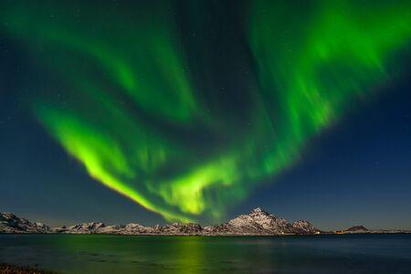 Aurore boréale, aurores boréales au-dessus des montagnes du fjord avec de nombreuses étoiles dans le ciel des îles Lofoten, Norvège, longue exposition