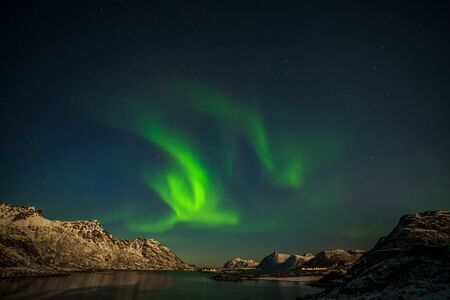 Aurora borealis, northern lights, northern lights, over fjord mountains with many stars on the sky in Lofoten islands, Norway, long shutter speed.