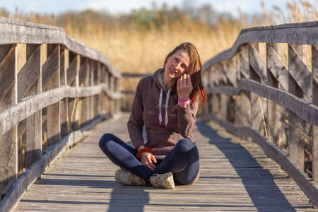 Red-haired girl siting on a wooden walkway looks at the camera and smiles Stockfoto