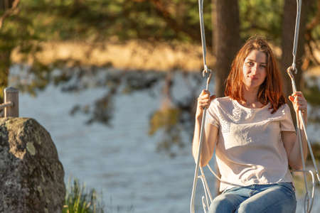 A young red-haired girl swinging on old swing at sunset time. Looks at the camera and smiles Stockfoto