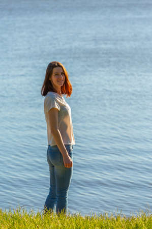 A red-haired girl in a T-shirt and jeans is walking along the lake. Looks at the camera and smiles