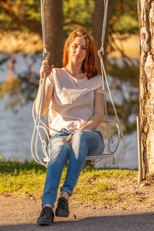 Beautiful red-haired girl on old swing at sunset time