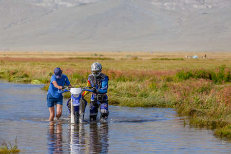 Altai, Mongolia - June 14, 2017: Two men are pushing a motorcycle along a road flooded with water. Altai, Mongolia Redactioneel