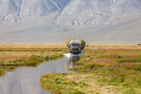 Altai, Mongolia - June 14, 2017: Truck carrying hay on a road covered with water after a flood. Altai, Mongolia