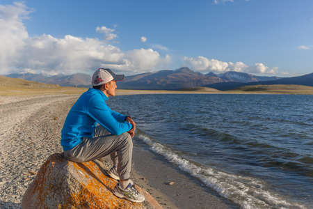 Altai, Mongolia - June 14, 2017: guy on stone on the shore of a mountain lake