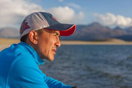 Altai, Mongolia - June 14, 2017: guy on the shore of a mountain lake.