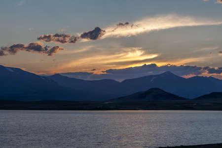 Beautiful blue ridge mountain sunset with orange sky. Mountain Lake in Mongolian Altai.