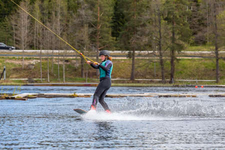 Fagersta, Sweden - Maj 26, 2020: Girl is riding a wakeboard on the lake. Wakeboard is Extreme Sports Redactioneel